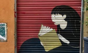 Street art piece of woman reading book in Genoa, Italy.