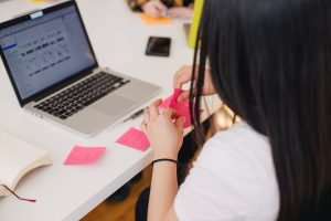 Photo of woman on computer with pink sticky notes.